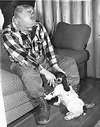 "Gordon MacQuarrie with his English Springer spaniel, ""Stuffy McGuffy"" at the cabin, ca. 1948."