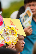 13 MAY 2013 - BANGKOK, THAILAND:  A man shades himself with the flag of the Royal Family and a fan depicting Bhumibol Adulyadej, the King of Thailand, and his wife, Queen Sirikit.  The Royal Plowing Ceremony is held Thailand to mark the traditional beginning of the rice-growing season. The date is usually in May, but is determined by court astrologers and varies year to year. During the ceremony, two sacred oxen are hitched to a wooden plough and plough a small field on Sanam Luang (across from the Grand Palace), while rice seed is sown by court Brahmins. After the ploughing, the oxen are offered plates of food, including rice, corn, green beans, sesame, fresh-cut grass, water and rice whisky. Depending on what the oxen eat, court astrologers and Brahmins make a prediction on whether the coming growing season will be bountiful or not. The ceremony is rooted in Brahman belief, and is held to ensure a good harvest. A similar ceremony is held in Cambodia.   PHOTO BY JACK KURTZ