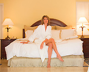 Female model relaxes in luxurious Fisher Island Club bedroom