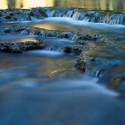 Light reflects on the water at the base of Havasu Falls, Havasu Canyon, AZ.