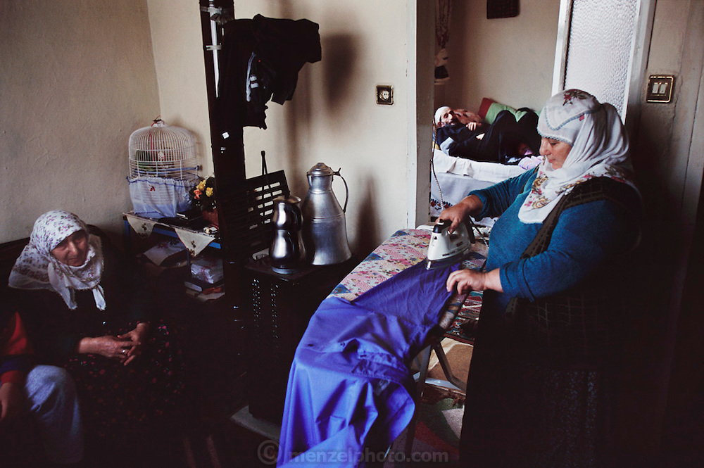 Safiye Çinar, 55, irons near the stove in her Golden Horn area home, Istanbul, Turkey in the background is the room where her parents Emine, 78, and Mehemet, 80 sleep.