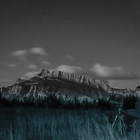 A photographer waits for moonrise in Banff National Park, Alberta, Canada.  Behind is Mount Rundle.
