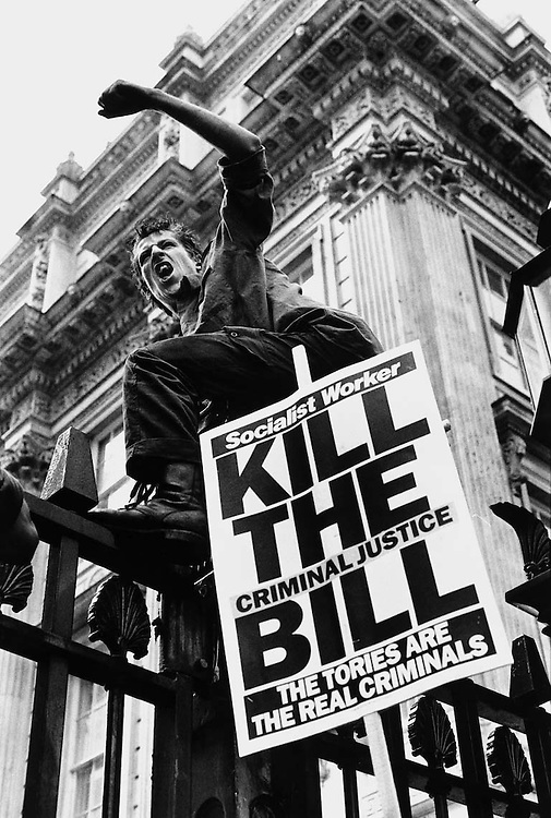 Protester on the gates outside Downing Street during a protest against, the criminal justice bill, London.