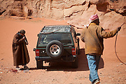 Bedouin men siphon gasoline by mouth from a jeep in the desert in Wadi Rum, Jordan.