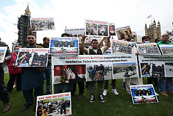 © Licensed to London News Pictures. 18/08/2021. London, UK. A group of former Afghan interpreters and their families stage a protest outside the Houses of Parliament. . Both houses fo Parliament have been recalled to discuss the ongoing situation in Afghanistan, where the Taliban have advanced quickly through the country after U. S troops started a full withdrawal . Photo credit: Ben Cawthra/LNP