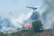 July 13, 2015 - Yorba Linda, CA, USA - <br /> <br /> water planes take to the sky to help put out fires<br /> <br /> A Cal-Fire helicopter drops water on a buring structure at Irvine Lake. A vegetation fire that grew to burn more than 100 acres Monday morning, threatened some structures near Irvine Lake and caused officials to close down Santiago Canyon Road in unincorporated Orange County, California<br /> ©Exclusivepix Media