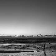 A man runs with his dog at Asilomar State Beach during sunset on Oct. 8, 2021.