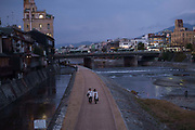 Couple taking an evening stroll down the banks of the Kamogawa River,