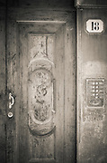 Wooden door and brass entry buzzer, Florence, Tuscany, Italy