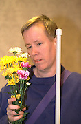 Blind musician age 36 holding bouquet of flowers. Exchange Charities Thanksgiving dinner Minneapolis Minnesota USA