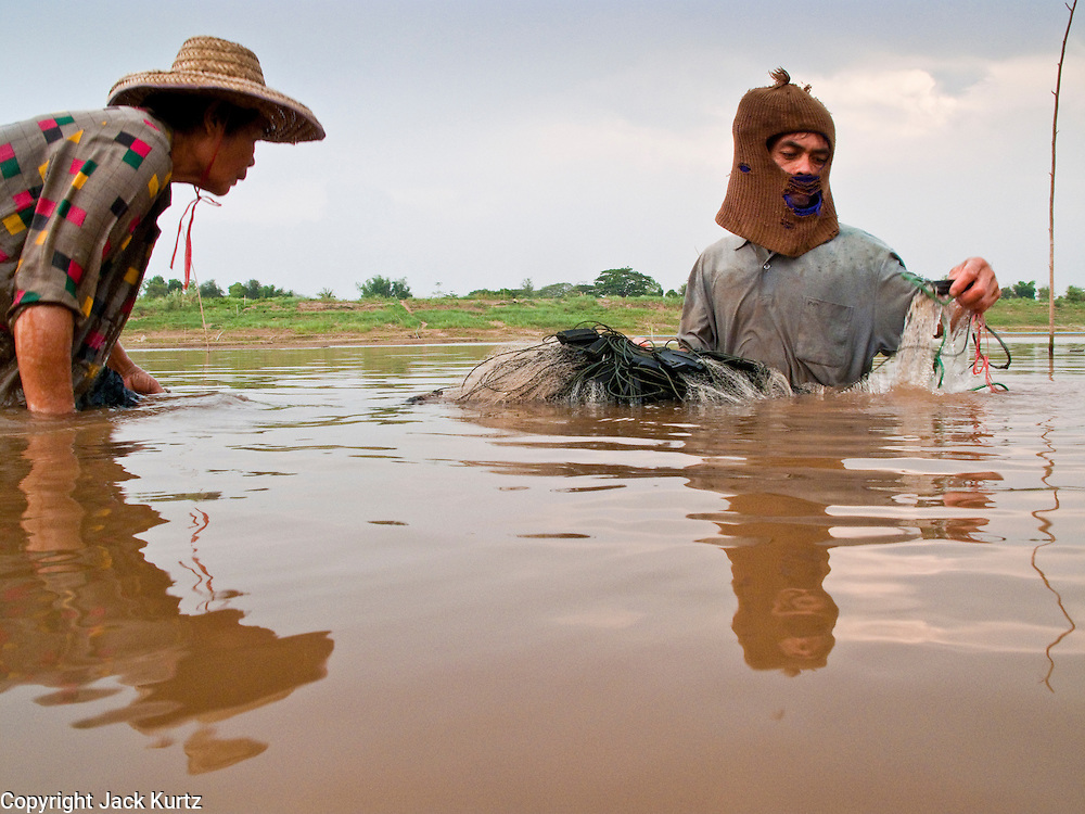 """07 APRIL 2010 - NAKHON PHANOM, THAILAND:  A couple nets fish in a channel in the Mekong River. They said they used to have use a boat for this but now the river is so low they do it on foot. He said he doesn't know why the river is so low, that some people say it's global warming. """"But I don't know what that is. I think it's when the factories send too much smoke into the air, but I don't understand it."""" He went onto to say that they catch much fewer fish now than they did in the past. Normally the river flows completely through the river bed but it's currently running through a channel in the bottom of the river bed. According to people who live here, the river is at its lowest point in nearly 50 years. Many of the people who live along the river farm and fish. They claim their crops yields are greatly reduced and that many days they return from fishing with empty nets. The river is so shallow now that fisherman who used to go out in boats now work from the banks and sandbars on foot or wade into the river.     PHOTO BY JACK KURTZ"""