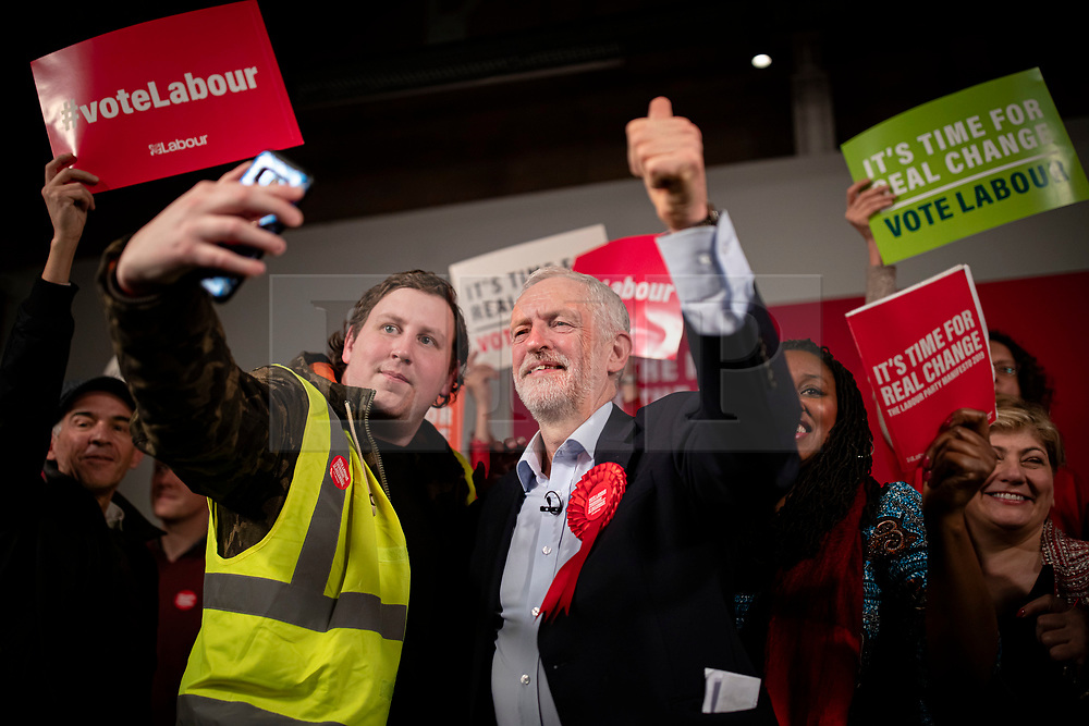 © Licensed to London News Pictures. 11/12/2019. London, UK. Leader of the Labour Party Jeremy Corbyn takes a selfie with a supporter on stage at the end of the party's final election rally of the campaign. Voters will head to polling stations tomorrow for the 2019 General Election. Photo credit: Rob Pinney/LNP