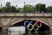 Triathletes run over Serpentine Bridge in London's Hyde Park for the Mens' Triathlon competition during the London 2012 Olympics, the 30th Olympiad. Serpentine Bridge marks the boundary between Hyde Park and Kensington Gardens. The Triathlon competitors raced over a 1.5km swim, a 43km bike race and a 10km run - eventually won by Team GB's Alistair Brownlee, Spain's Javier Gomez and Jonathan Brownlee (brother of the winner). The Serpentine (also known as the Serpentine River) is a 28-acre (11 ha) recreational lake in Hyde Park, London, England, created in 1730. The venue was the Hyde Park 142 hectares (350 acres) Hyde Park in the heart of the capital, one of the largest parks in central London and the site of the Victorian Great Exhibition of 1851.
