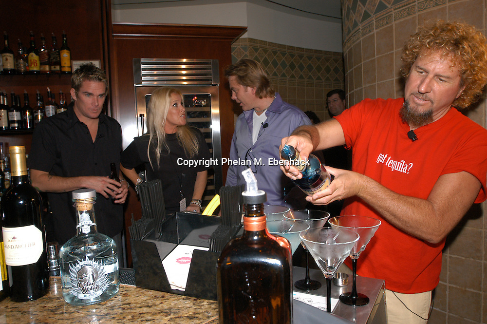 Rocker Sammy Hagar, right, mixes a drink as Mark McGrath, of Sugar Ray, left, Lita Ford, and Hard Rock Hotel general manager Lou Carrier wait during the opening of The Kitchen restaurant at the Hard Rock Cafe Hotel at the Universal Orlando Resort in Orlando, Florida.