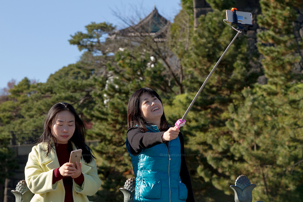 Asian  tourists with a selfie stick and an iPhone stakes a selfie at the Imperial Palace in Tokyo, Japan. Friday December 18th 2015