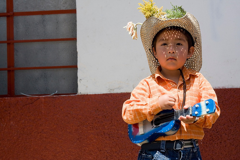 A young boy plays a toy guitar during a parde in Paracho, Michoacan state, Mexico on August 10, 2008 during the annual Feria Internacional de la Guitarra. Parades for different professions are held each day of the weeks-long festival, culminating in the parade of the guitar makers.