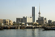 Skyline of Kuwait City with ancient doha fishing boats along the waterfront of the Persian Gulf.