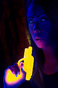 Young woman blowing the smoke off of a glowing pistol.Black light
