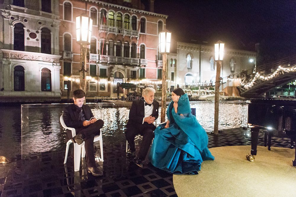 """VENICE, ITALY - 13 JULY 2016: (R-L) Actress Monica Bellucci (51), conductor and tenor Placido Domingo (75) and actor Gael Garcia Bernal (37) wait on the set and barge before shooting a scene of an episode of the third season of """"Mozart in the Jungle"""" on the Grand Canal in Venice, Italy, on July 13th 2016.<br /> <br /> Mozart in the Jungle is an award-winning television series produced by Picrow for Amazon Studios. The pilot was written by Roman Coppola, Jason Schwartzman, and Alex Timbers and directed by Paul Weitz. The story was inspired by Mozart in the Jungle: Sex, Drugs, and Classical Music, oboist Blair Tindall's 2005 memoir of her professional career in New York."""