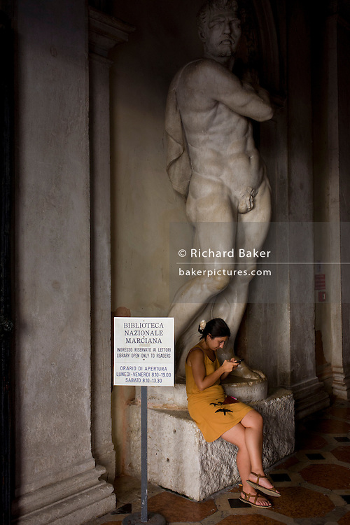 Girl checks messages outside the entrance of the Biblioteca Nazionale Marciana in the covered Procuratie Nuovo of Piazza San Marco, Venice, Italy.