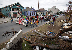 16 Jan, 2006. New Orleans, Louisiana. Post Katrina.<br /> Martin Luther King Jr parade. passing piles of debris in the lower Ninth Ward, the C3/Hands off Iberville coalition march almost 6 miles from the devastated Lower Ninth Ward to downtown New Orleans in an alternative protest to the Mayor's officially sanctioned celebrations marking Martin Luther King Jr day. The protest remembered those who perished and claims to stand up for the rights of displaced, primarily african americans.<br /> Photo; Charlie Varley/varleypix.com