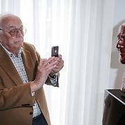 NLD/Amsterdam/20120419 - Onthulling beeld Johnny Kraaijkamp Sr., Leen Timp maakt met zijn Ipone foto van het bronzen beeld