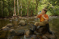 A boy drinks from the pure water of a river in Borneo.