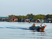 A small boat travelling through a floating village community on the great Tonlé Sap lake, Cambodia