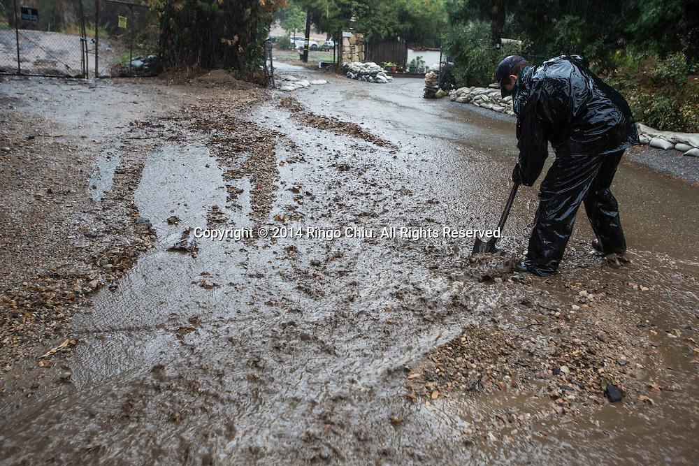 12月2日,美國加利福尼亞州洛杉磯,一名民眾正在清理從山上流下來的泥和碎片。當天南加州迎來秋天第一場暴雨,將為今年面臨嚴重乾旱問題的加州帶來2至5寸雨水。 同時,當局亦發出警告,洪水、土石流可能會襲擊部分地區。 (新華社發 趙漢榮攝) <br />  A man works to stem mud and debris flowing down a hillside from the burnt areas in Los Angeles, California, Tuesday, December 2, 2014. California is bracing for the arrival of a new, more powerful Pacific storm following a weekend of scattered rain, showers and snow. The National Weather Service says a low-pressure system off the coast will draw a plume of subtropical moisture northward into the state beginning on Tuesday.  (Xinhua/Zhao Hanrong)(Photo by Ringo Chiu/PHOTOFORMULA.com)