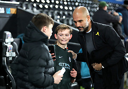 Manchester City manager Pep Guardiola takes a picture with a young fan as he arrives at the stadium prior to the Premier League match at the Liberty Stadium, Swansea.