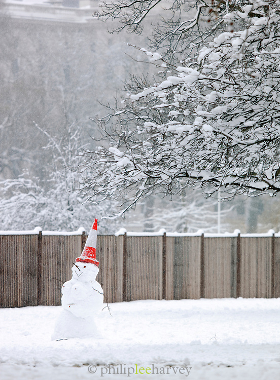 A snowman with a traffic cone on his head in St James Park, London, UK