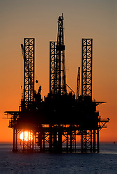 Offshore jackup oil drilling rig silhouetted at sunset in the Gulf of Mexico.