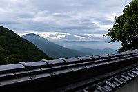 """Shikoku Hills - As interesting as the Shikoku Pilgrimage may be as an epic odyssey, tramping from one temple to another sometimes many kilometers apart, takes its toll and some pilgrims fail to smell the flowers along the way.  Until very recently when bridges were built over the Inland Sea, Shikoku had long been considered a kind of backwater only approached by boat.  This lack of development is in fact one of Shikoku's very charms.  The island also has a reputation of being """"slow"""" - Tokyoites will be frustrated by the waiter's failure to bring their coffee instantly, and may very well find the cafe's staff taking a nap midday - a custom almost unthinkable elsewhere in Japan"""