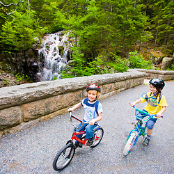 two young bike riders on a carriage road in Maine's Acadia National Park.  Hadlock Brook, Waterfall Bridge.