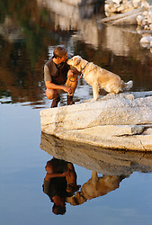 Man and dog together at the end of a rock in a lake