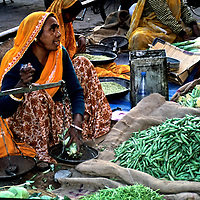 Asia, India, Ajmer. Woman in colorful sari sells beans in stret market.