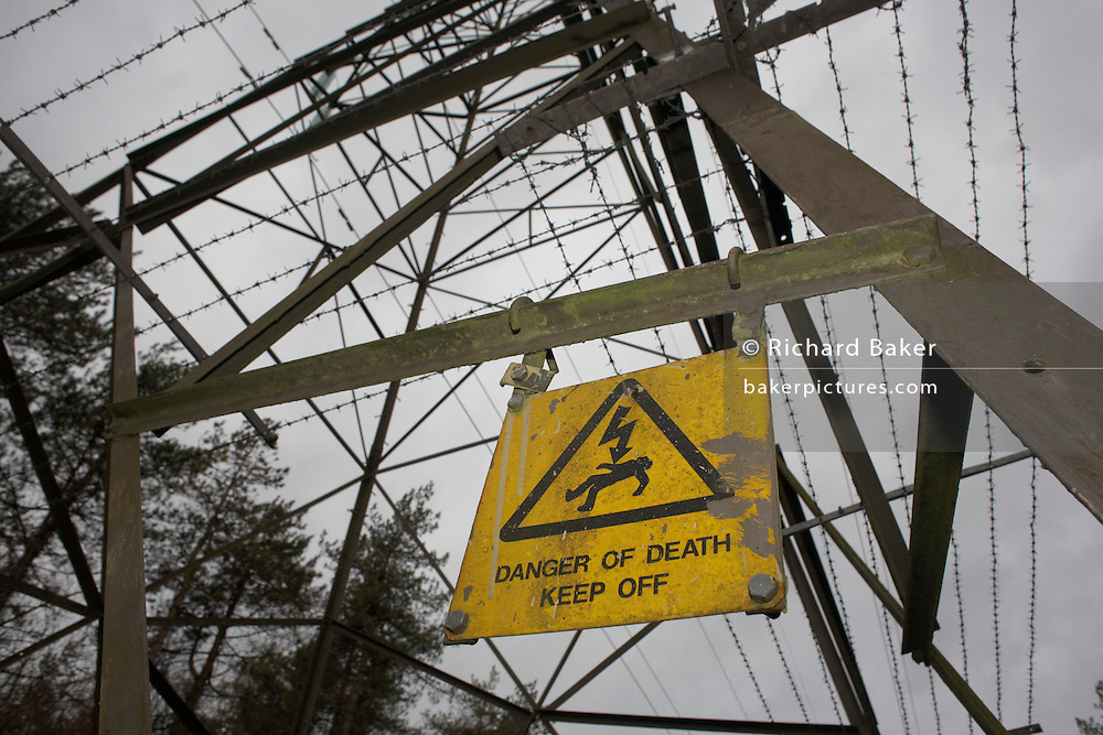 A sign showing instant death warns anyone climbing this electricity pylon standing in woodland near Wrington, North Somerset England.