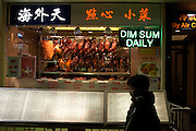 A passer-by stands next to a menu from a Chinese restaurant in Gerrard Street in London's Chinatown, England. The words Dim Sum Daily are displayed in neon lights above the person's head, its translated message is written on the top in Chinese characters. In the clear window we can see rows of Peking duck. It is early evening and the street is full of colour from the artificial lighting that creates an inviting mood for those browsing the menus on offer in this lively part of London's West End. The pedestrian is partly silhouetted and she stands in profile looking straight ahead as if ignoring what is on offer.