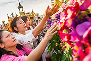 06 JANUARY 2013 - BANGKOK, THAILAND:  Women cry out and try to reach a relic that is a piece of the Buddha's hair as the truck carrying the relic leaves a special service for it in Bangkok Sunday. The relic has been on display in Bangkok for about 10 years. There was a ceremony in Sanam Luang in Bangkok Sunday to honor the relic. People prayed for it and received blessings from Buddhist monks and Brahmin priests who presided over the service. The hair is being moved to Ayutthaya, where it will be displayed in a Buddhist temple. The piece of hair has been on loan to Thai Buddhists from a Buddhist temple in Sri Lanka.   PHOTO BY JACK KURTZ