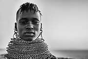 A portrait in black and white of a Turkana girl wearing traditional stacked beaded necklaces, Lake Turkana, Loiyangalani,Kenya, Africa