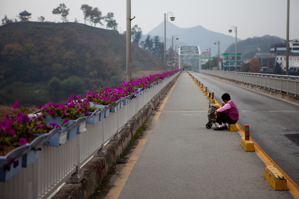 Korean woman resting on the Geungang bridge over the Geum river in Gongju. This Korean city was the second capital of the Baekje kingdom from AD 475 for 70 years. / Gongju, South Korea, Republic of Korea, KOR, 31 October 2009.