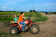 10162247A DYESS, Ark. - Aug. 11, 2014 - Harley Murphy, 5, of Dyess, left, lets out a laugh while riding a three-wheeler with her mother, Amy Murphy, along the dirt roads in Mississippi County. CREDIT William DeShazer for the New York Times