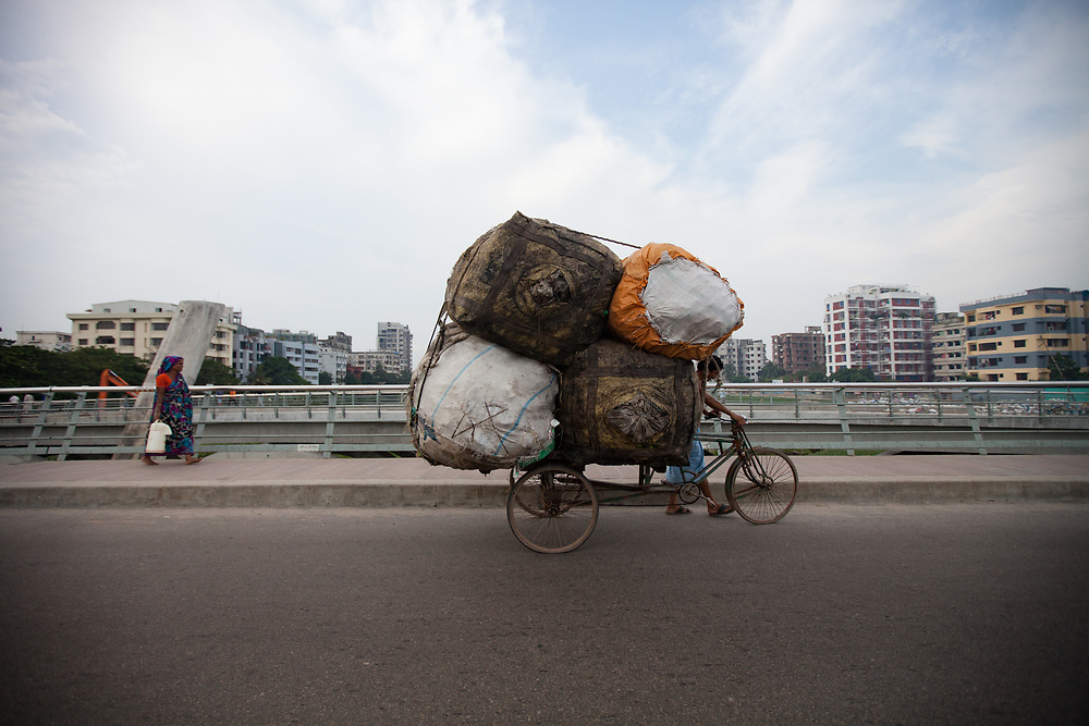 A rickshaw driver carries a huge load in Dhaka, Bangaldesh