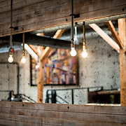 Bare lightbulbs hang in front of a large wall mirror in a renovated historic building now housing a restaurant.