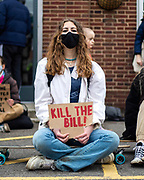 """Women holding a sign """"Kill the bill"""" sitting at the entrance to Alex Chalk's offices, Cheltenham's MP. 20/03/2021"""