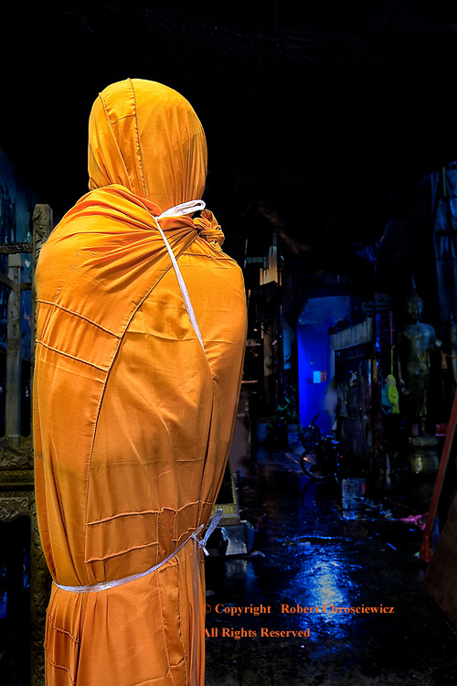 Restrained / Selfie: A newly minted Buddha is bound in a saffron cloth, not unlike a kidnapped victim, or, one restrained by their upbringing, societal standards or religion; left alone in a dark, dismal place, Bangkok Thailand.