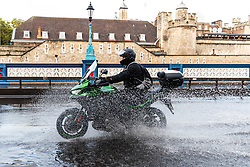 © Licensed to London News Pictures. 06/10/2019. London, UK. A motorcyclist drives through flooding and excess surface water on Tower Bridge this morning following heavy rain and wet weather in the capital last night. Weather forecasts predict that most of the UK will be experience heavy rain and storms during the next few days. Photo credit: Vickie Flores/LNP