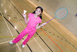 Young girl enjoying playing a game of badminton in the sports hall of her local leisure centre,