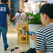THA/Pattaya/20180722 - Vakantie Thailand 2018, Thai wachtend in winkelcentrum, ondertussen op zijn telefoon filmpje aan het kijken