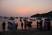 The beach at dusk sunset in Taganga, with silhouetted fishing boats coming in to land after a day at sea. Santa Marta district, Colombia.